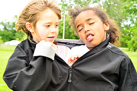 two girls sharing one coat