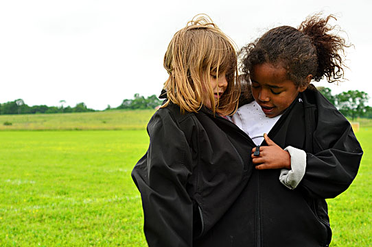 Two girls sharing a coat