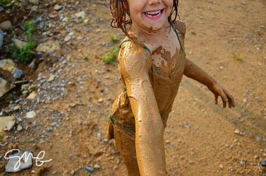 Muddy kid reaching for cameraman