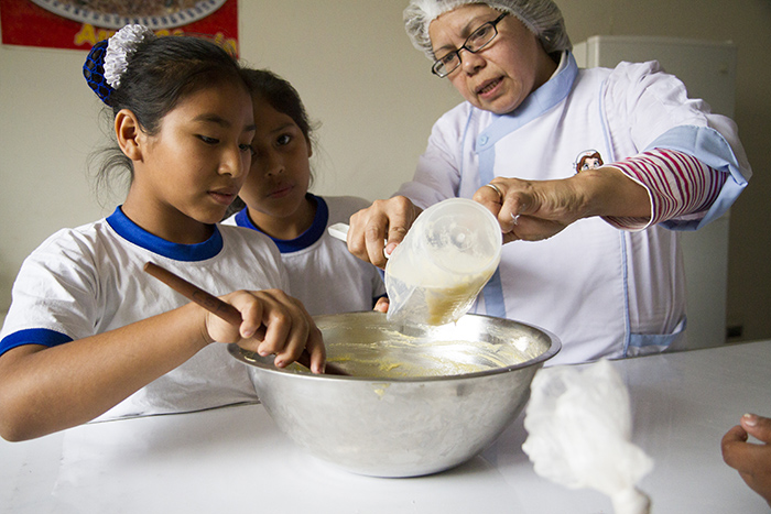 Maria teaching children to cook