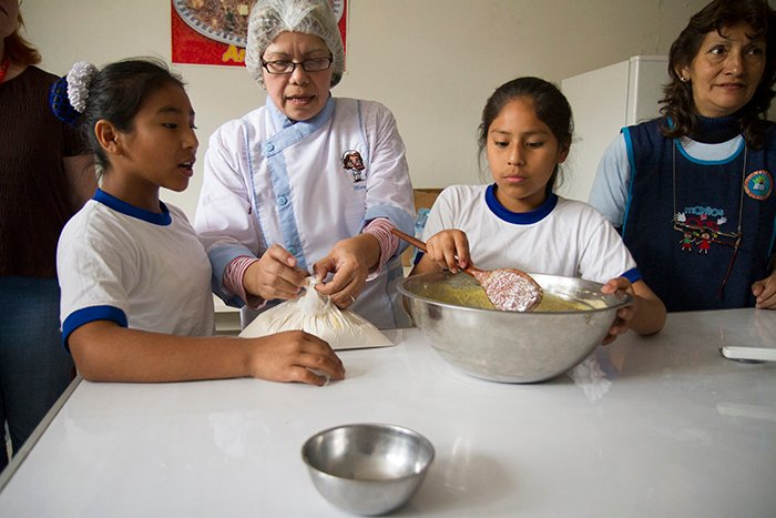 Maria teaching girls to cook